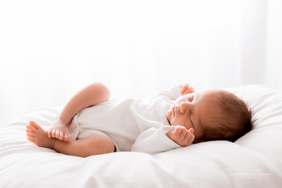 na miękkiej białej poduszce śpi noworodek ubrany w białe body